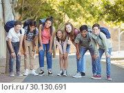 Купить «Portrait of happy students standing with schoolbag on road», фото № 30130691, снято 19 ноября 2016 г. (c) Wavebreak Media / Фотобанк Лори