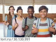 Купить «Portrait of happy students standing with schoolbags in campus», фото № 30130991, снято 20 ноября 2016 г. (c) Wavebreak Media / Фотобанк Лори