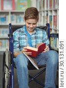 Купить «Disabled schoolboy reading book in library», фото № 30131091, снято 20 ноября 2016 г. (c) Wavebreak Media / Фотобанк Лори