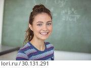 Купить «Portrait of happy schoolgirl in classroom», фото № 30131291, снято 20 ноября 2016 г. (c) Wavebreak Media / Фотобанк Лори