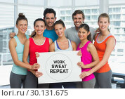 Купить «Group of people holding card with text  work, sweat and repeat in front of window in gym», фото № 30131675, снято 25 января 2017 г. (c) Wavebreak Media / Фотобанк Лори