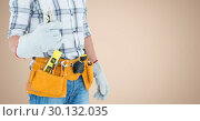 Handy man standing with tools against beige background. Стоковое фото, агентство Wavebreak Media / Фотобанк Лори