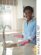 Купить «Portrait of woman cleaning utensils in kitchen sink», фото № 30132187, снято 16 ноября 2016 г. (c) Wavebreak Media / Фотобанк Лори
