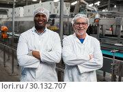 Купить «Portrait of two factory engineers standing with arms crossed», фото № 30132707, снято 20 октября 2016 г. (c) Wavebreak Media / Фотобанк Лори