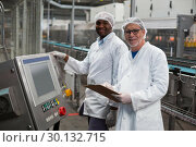 Купить «Two factory engineers standing near machine in factory», фото № 30132715, снято 20 октября 2016 г. (c) Wavebreak Media / Фотобанк Лори