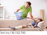 Купить «Husband helping leg injured wife in housework», фото № 30132743, снято 4 октября 2018 г. (c) Elnur / Фотобанк Лори