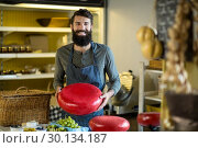 Купить «Smiling salesman holding a gouda cheese», фото № 30134187, снято 4 октября 2016 г. (c) Wavebreak Media / Фотобанк Лори