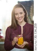 Купить «Shop assistant holding a jar of pickle in grocery shop», фото № 30134259, снято 4 октября 2016 г. (c) Wavebreak Media / Фотобанк Лори