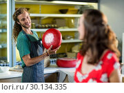 Купить «Salesman holding gouda cheese and interacting with costumer», фото № 30134335, снято 4 октября 2016 г. (c) Wavebreak Media / Фотобанк Лори