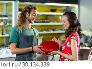 Купить «Salesman assisting costumer in buying gouda cheese at counter», фото № 30134339, снято 4 октября 2016 г. (c) Wavebreak Media / Фотобанк Лори