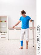 Купить «Leg injured young man with crutches at home», фото № 30135235, снято 19 сентября 2018 г. (c) Elnur / Фотобанк Лори