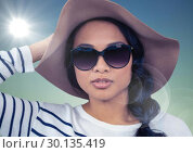 Купить «Woman in summer hat against blue background with flare», фото № 30135419, снято 6 февраля 2017 г. (c) Wavebreak Media / Фотобанк Лори