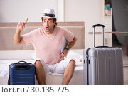 Купить «Man with suitcase in bedroom waiting for trip», фото № 30135775, снято 17 сентября 2018 г. (c) Elnur / Фотобанк Лори