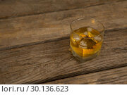 Купить «Glass of whisky with ice on wooden table», фото № 30136623, снято 11 января 2017 г. (c) Wavebreak Media / Фотобанк Лори