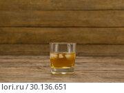 Купить «Glass of whisky with ice cube», фото № 30136651, снято 11 января 2017 г. (c) Wavebreak Media / Фотобанк Лори