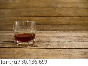 Купить «Glass of whisky on wooden table», фото № 30136699, снято 11 января 2017 г. (c) Wavebreak Media / Фотобанк Лори