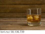Купить «Glass of whisky with ice cube on wooden table», фото № 30136739, снято 11 января 2017 г. (c) Wavebreak Media / Фотобанк Лори