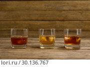 Купить «Three glasses of whiskey with ice cube», фото № 30136767, снято 11 января 2017 г. (c) Wavebreak Media / Фотобанк Лори