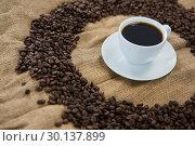Купить «Coffee cup with coffee beans arranged on sack», фото № 30137899, снято 6 октября 2016 г. (c) Wavebreak Media / Фотобанк Лори