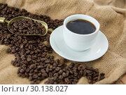 Купить «Black coffee, roasted beans and scoop on sack», фото № 30138027, снято 6 октября 2016 г. (c) Wavebreak Media / Фотобанк Лори