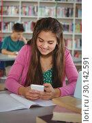 Купить «Smiling schoolgirl using mobile phone in library», фото № 30142591, снято 20 ноября 2016 г. (c) Wavebreak Media / Фотобанк Лори