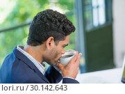Купить «Businessman having coffee», фото № 30142643, снято 21 ноября 2016 г. (c) Wavebreak Media / Фотобанк Лори