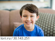 Купить «Portrait of smiling boy sitting on sofa in living room», фото № 30143251, снято 29 ноября 2016 г. (c) Wavebreak Media / Фотобанк Лори