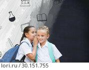 Купить «Schoolgirls whispering with school items on blackboard», фото № 30151755, снято 24 июля 2017 г. (c) Wavebreak Media / Фотобанк Лори