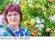 Купить «Portrait of a smiling middle-aged woman against the background of a flowering tree.», фото № 30159059, снято 25 августа 2018 г. (c) Акиньшин Владимир / Фотобанк Лори