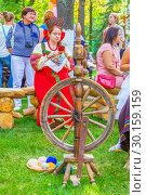 Купить «Russia Samara August 2018: Flower Festival. Historical reconstruction of rural life. The girl in the Russian national costume is engaged in embroidery. Nearby there is a spinning wheel with threads.», фото № 30159159, снято 25 августа 2018 г. (c) Акиньшин Владимир / Фотобанк Лори