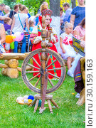 Купить «Russia Samara August 2018: Flower Festival. Historical reconstruction of rural life. The girl in the Russian national costume is engaged in embroidery. Nearby there is a spinning wheel with threads.», фото № 30159163, снято 25 августа 2018 г. (c) Акиньшин Владимир / Фотобанк Лори