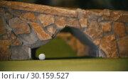 Купить «Playing mini golf. A little ball is rolling on the field under the bridge», видеоролик № 30159527, снято 25 марта 2019 г. (c) Константин Шишкин / Фотобанк Лори