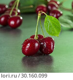 Купить «Fresh juicy berries cherries with green leaves in drops on dark table», фото № 30160099, снято 14 июня 2018 г. (c) Сергей Молодиков / Фотобанк Лори