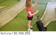 Купить «Playing mini golf. A young blonde woman comes to the bag and taking a golf stick», видеоролик № 30160355, снято 25 марта 2019 г. (c) Константин Шишкин / Фотобанк Лори