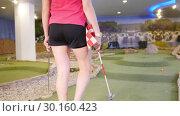Купить «A young woman playing mini golf. Taking a finish flag and stands it near the hole», видеоролик № 30160423, снято 25 марта 2019 г. (c) Константин Шишкин / Фотобанк Лори
