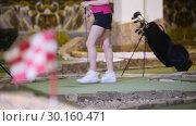 Купить «A young woman playing mini golf. Finishing flag on the blured foreground», видеоролик № 30160471, снято 25 марта 2019 г. (c) Константин Шишкин / Фотобанк Лори