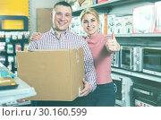 Купить «Couple with packed purchases holding thumbs up in appliances store», фото № 30160599, снято 1 марта 2018 г. (c) Яков Филимонов / Фотобанк Лори