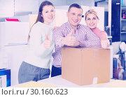 Купить «Positive family of three holding thumbs up in store with packed household appliances», фото № 30160623, снято 1 марта 2018 г. (c) Яков Филимонов / Фотобанк Лори