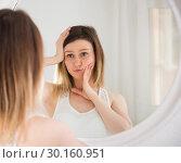 Купить «Young woman using mirror and touching face in bedroom», фото № 30160951, снято 23 апреля 2018 г. (c) Яков Филимонов / Фотобанк Лори