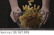 Transparent glass bowl in a woman's hands with pouring raw colorful Italian pasta on a wooden rustic table on a black. Slow motion, Full HD video, 240fps, 1080p. Стоковое видео, видеограф Ярослав Данильченко / Фотобанк Лори