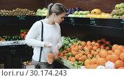 Купить «Smiling woman customer choosing fresh fruits on the market», видеоролик № 30174243, снято 12 февраля 2019 г. (c) Яков Филимонов / Фотобанк Лори