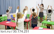 Купить «Portrait of schoolchildren with teacher performing daily physical exercises in classroom during break on lesson», видеоролик № 30174251, снято 30 января 2019 г. (c) Яков Филимонов / Фотобанк Лори