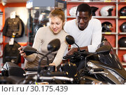 Купить «Portrait of satisfied man and woman looking new motorbike at motosalon showroom», фото № 30175439, снято 16 января 2019 г. (c) Яков Филимонов / Фотобанк Лори