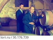 two working men in uniforms taking notes in cellar with wine woods. Стоковое фото, фотограф Яков Филимонов / Фотобанк Лори