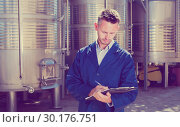 Купить «young friendly man working in winery and taking notes», фото № 30176751, снято 21 марта 2019 г. (c) Яков Филимонов / Фотобанк Лори