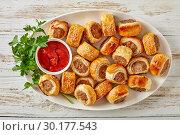 Купить «sausage rolls on a white oval platter», фото № 30177543, снято 19 февраля 2019 г. (c) Oksana Zh / Фотобанк Лори