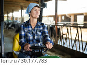Купить «Adult female farmer is sitting in the car near cows», фото № 30177783, снято 24 октября 2017 г. (c) Яков Филимонов / Фотобанк Лори