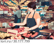 Купить «Woman seller is demonstraiting red tomatos in the store.», фото № 30177799, снято 22 октября 2017 г. (c) Яков Филимонов / Фотобанк Лори