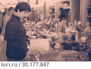 Купить «Portrait of senior woman choosing vintage goods at flea market», фото № 30177847, снято 23 октября 2017 г. (c) Яков Филимонов / Фотобанк Лори