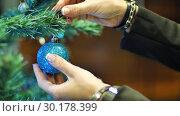 Female hands hanging balls on the Christmas tree. Winter holidays Christmas and New Year Decoration. Blinking Garland. Christmas Tree Lights Twinkling. Стоковое фото, фотограф Uladzimir Sitkouski / Фотобанк Лори